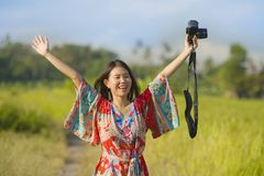 Sweet young Asian Chinese or Korean woman on her 20s posing happy and playful holding photo camera smiling happy in beautiful natu. Re landscape in holidays and Stock Photo