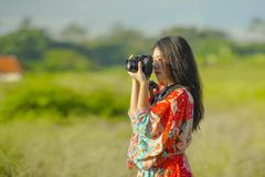 Sweet young Asian Chinese or Korean woman on her 20s taking picture with photo camera smiling happy in beautiful nature landscape. In holidays and photographer Royalty Free Stock Photo