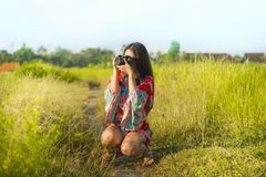 Sweet young Asian Chinese or Korean woman on her 20s taking picture with photo camera smiling happy in beautiful nature landscape. In holidays and photographer Royalty Free Stock Photos