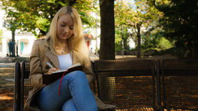 Sweet young blond women. Sweet young blond woman writing in her diary royalty free stock images