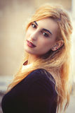 Sweet young blonde girl. Youthful fine beauty. Emotional pose. Portrait of a beautiful young Italian girl. Bright eyes and soft colors. Love and romance concept stock photo