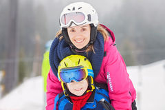 Sweet young boy and his mother, learning to ski on a mild ski sl Royalty Free Stock Photos