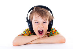 Sweet young boy listening to music on headphones. Portrait of a sweet young boy listening to music on headphones against white background stock photo