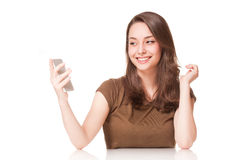Sweet young brunette using mobile phone. Royalty Free Stock Photo