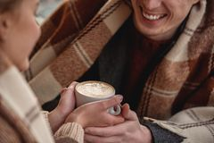 Sweet young couple holding cup of hot drink together Stock Photos