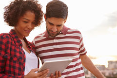 Sweet young couple looking at tablet Royalty Free Stock Photo