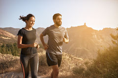 Sweet young couple running in the mountains Royalty Free Stock Images