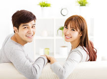 Sweet young couple sitting in sofa royalty free stock photography