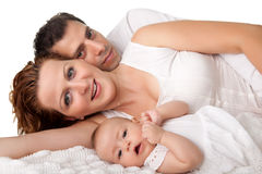 Sweet young family lying together on bed royalty free stock images