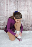 Sweet young figure skater tying her skates Royalty Free Stock Photography