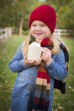 Sweet Young Girl Holding Cocoa Mug with Marsh Mallows Outside. Cute Smiling Young Girl Wearing Hat and Scarf Holding Cocoa Mug with Marsh Mallows Outside Royalty Free Stock Photos