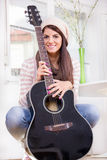 Sweet young girl holding the guitar Royalty Free Stock Photography