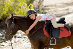 Sweet young girl hugging pony horse smiling happy wearing safety jockey helmet in summer holiday Royalty Free Stock Photography