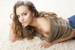 Sweet young girl laying on carpet with hand near t Stock Images