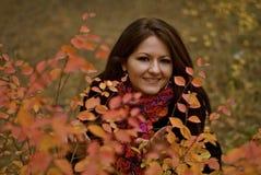 Sweet young girl and nice bush Royalty Free Stock Photos