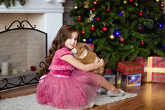 Sweet young girl in a pink dress sitting near the fireplace in t stock photo