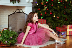 Sweet young girl in a pink dress smiles and sits near the firepl Royalty Free Stock Photos