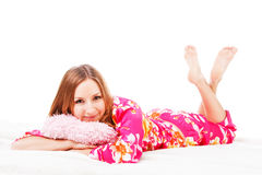Sweet young girl in pink pajamas on bed Royalty Free Stock Photos