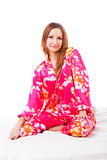 Sweet young girl in pink pajamas on bed Stock Photography