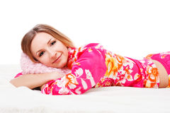 Sweet young girl in pink pajamas on bed Stock Photos