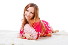 Sweet young girl in pink pajamas on bed Stock Images