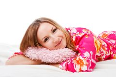 Sweet young girl in pink pajamas on bed Royalty Free Stock Photography
