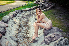 Sweet young girl sitting on rock by stream Stock Photo