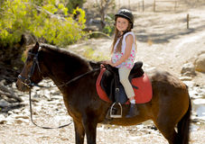 Sweet young girl 7 or 8 years old riding pony horse smiling happy wearing safety jockey helmet in summer holiday Royalty Free Stock Photo