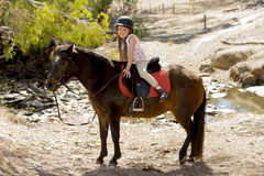Sweet young girl 7 or 8 years old riding pony horse smiling happy wearing safety jockey helmet in summer holiday Stock Image