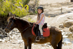 Sweet young girl 7 or 8 years old riding pony horse smiling happy wearing safety jockey helmet in summer holiday Royalty Free Stock Image