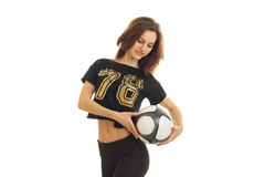 Sweet young gymnast in black t-shirt holding a soccer ball looking down and smiling. Isolated on white background Royalty Free Stock Images