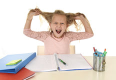 Sweet young little schoolgirl pulling her hair desperate in stress while sitting on school desk doing homework tired Stock Photography
