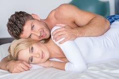 Sweet Young Lovers Lying on Bed Looking at Cam stock image