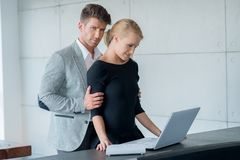 Sweet Young Lovers Using Laptop on Table Stock Images