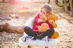 Sweet Young Mixed Race Girl Hugging Teddy Bear Outdoors. Cute Young Mixed Race Girl Hugging Teddy Bear Outdoors royalty free stock images