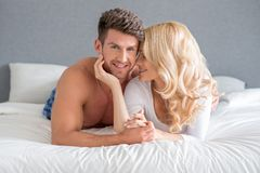 Sweet Young White Couple Lying on Bed Stock Photography