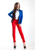 Sweet young woman in red pants and blue coat Stock Photography