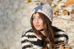 Sweet young woman standing among yellow leaves. Very sweet and pretty young woman outdoor, wear winter knitted cap standing among yellow leaves royalty free stock images
