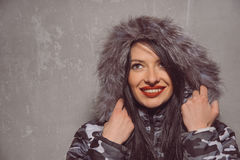 Sweet young woman in warm winter jacket with fur hood Royalty Free Stock Photography