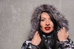 Sweet young woman in warm winter jacket with fur hood Stock Photos