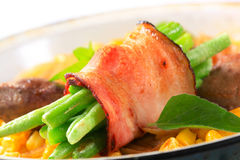 Sweetcorn with fried chicken liver and green beans in bacon. Sweetcorn with fried chicken liver and bacon wrapped green beans Royalty Free Stock Image