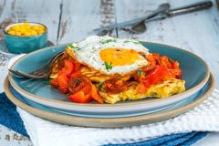 Sweetcorn pancakes with fried egg and chorizo salsa. Sweetcorn pancakes with fried egg and chorizo and red pepper salsa royalty free stock photo