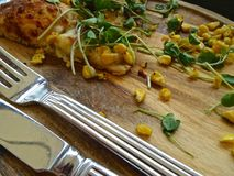 Sweetcorn pizza leftovers. On a wooden board, with knife and fork Stock Photos