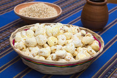Sweetened Popped Pasta, a Bolivian Snack. Sweetened popped white corn called Pasancalla eaten as snack in Bolivia served in a woven basket with coca tea in the Stock Photo