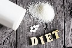 Sweetener tablet and sugar. Text diet wooden letters. Food stock image