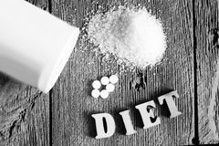 Sweetener tablet and sugar. Text diet wooden letters. Food stock photos