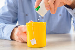 Sweetener. Tablets and hand with box whit cup of tea Stock Photo