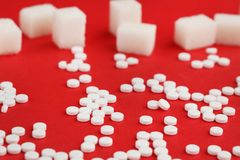 Sweetener tablets. And sugar cubes on red background Stock Photography
