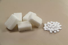 Sweetener tablets and sugar cubes. Sweetener tablets beside sugar cubes on a table Stock Image