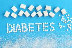 Sweetener tablets. And sugar cubes with inscription Diabetes on blue background Stock Images